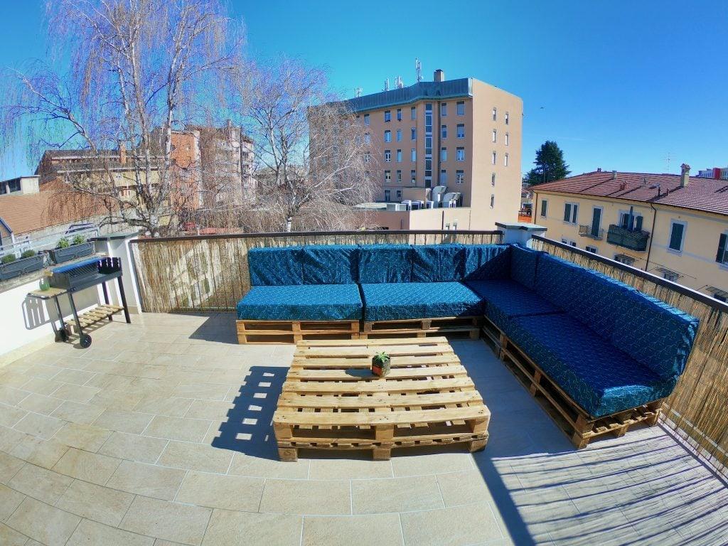 Terrazzo con griglia e divano fatto di bancali al Travellers' Loft a Varese